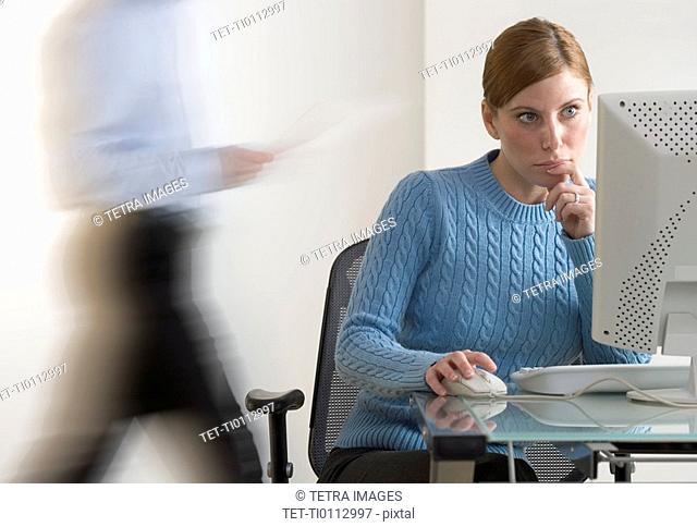 Woman at computer with person passing