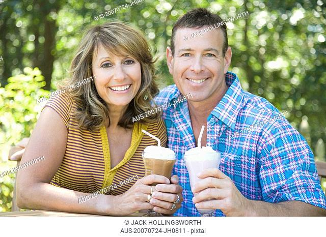 Portrait of a mature couple holding milk shakes and smiling
