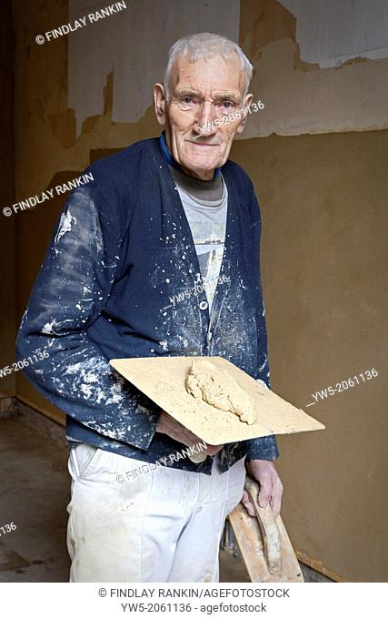 75 year old master plasterer, working at Fairfield, Govan Road, Glasgow, Scotland, UK during the restoration. He's holding plasterers tools with fine lime...