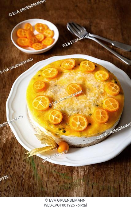 Mango passion fruit cake decorated with slices of kumquat