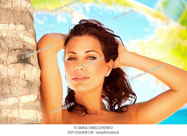Portrait of a beautiful gorgeous female standing on the beach near palm tree, woman enjoying sunny days on tropical resort