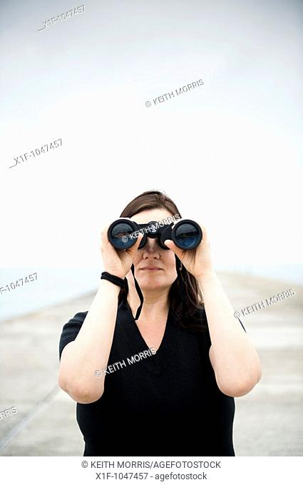 A woman looking through a pair of binoculars