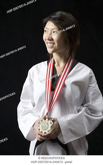 Young woman standing with a medal around her neck