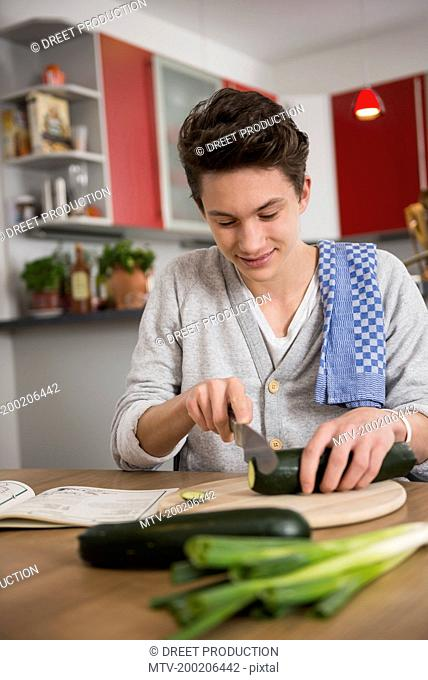 Young man helping recipe book with preparing food in kitchen, Munich, Bavaria, Germany
