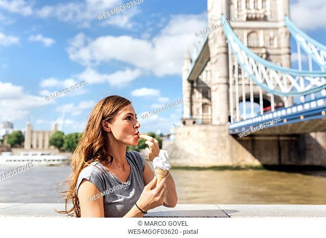 UK, London, woman eating an ice cream near the Tower Bridge