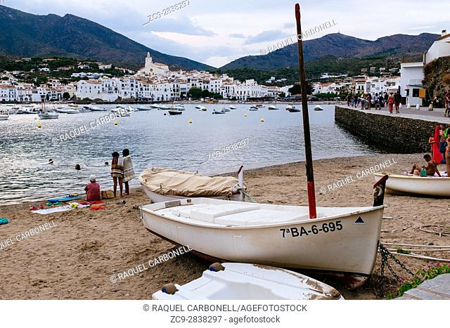 People and boats at the beach in front of the white village. Cadaqués, Alt Amporda, Girona province, Catalonia, Spain