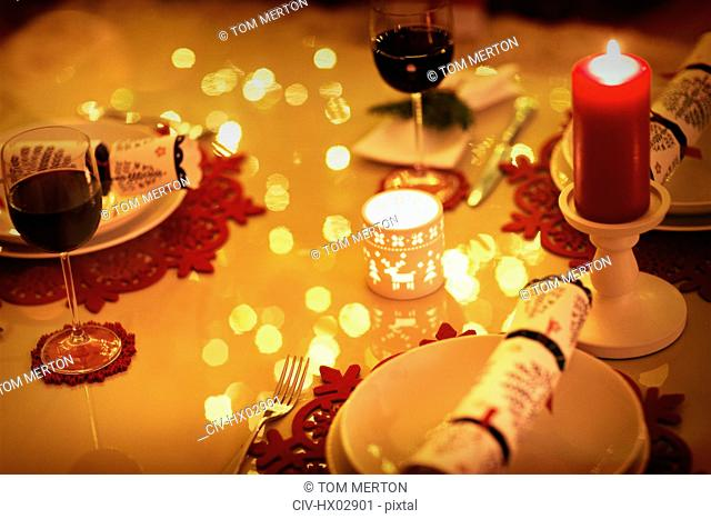 Red wine and candles on ambient Christmas dinner table