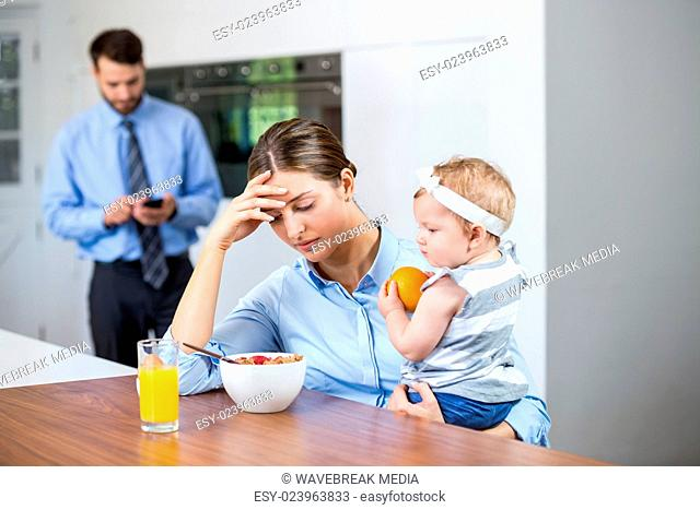Tensed woman with daughter while husband in background