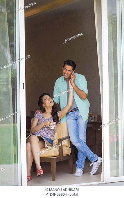 India, Woman taking away phone from man talking nearby