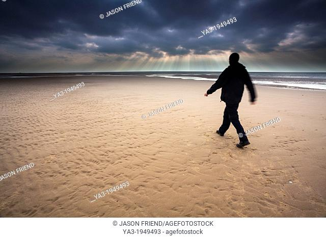 England, Lancashire, Blackpool. Hiker walking along the South Shore beach with distant storm above the Irish Sea