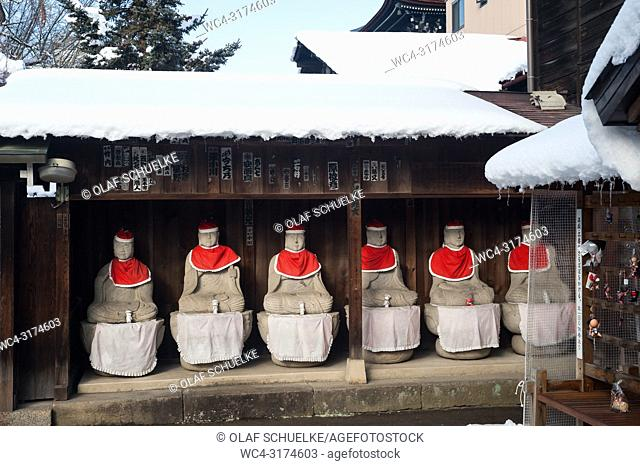 Takayama, Gifu, Japan, Asia - A row of Jizo statues made of stone, wearing red hats and bibs is seen sitting under a wooden shelter at the Hida Kokubun-ji...