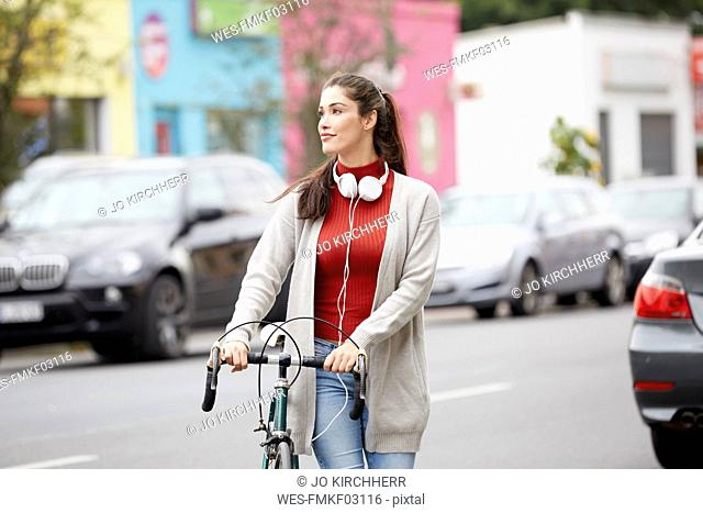 Relaxed woman with headphones and bicycle crossing the street