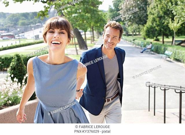 Couple walking on a walkway in a garden, Eiffel Tower, Paris, Ile-de-France, France