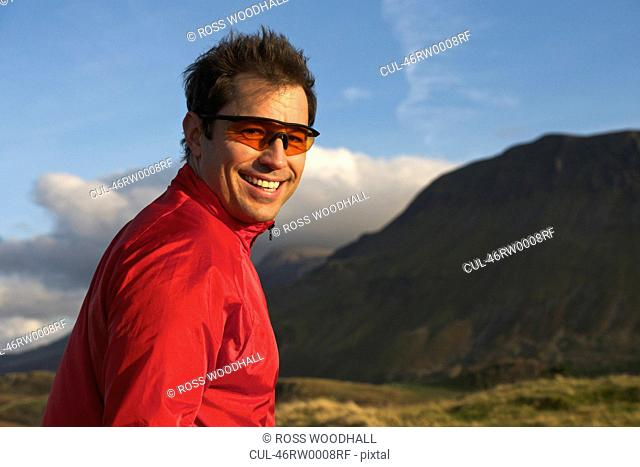 Hiker smiling in rural landscape