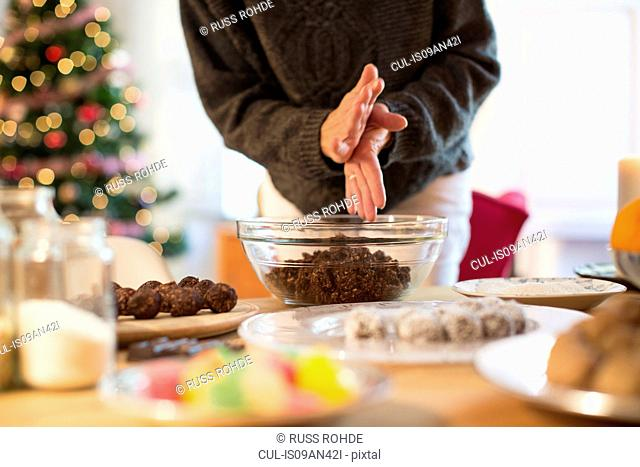 Preparing christmas (chocolate, coconut, oat) truffles at kitchen counter