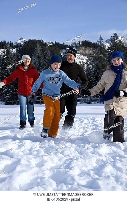 Family running through the snow