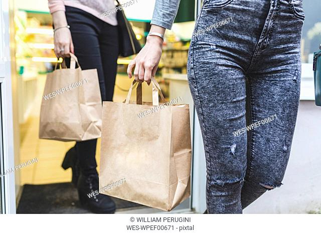 Close-up of two women leaving shop holding paper bags
