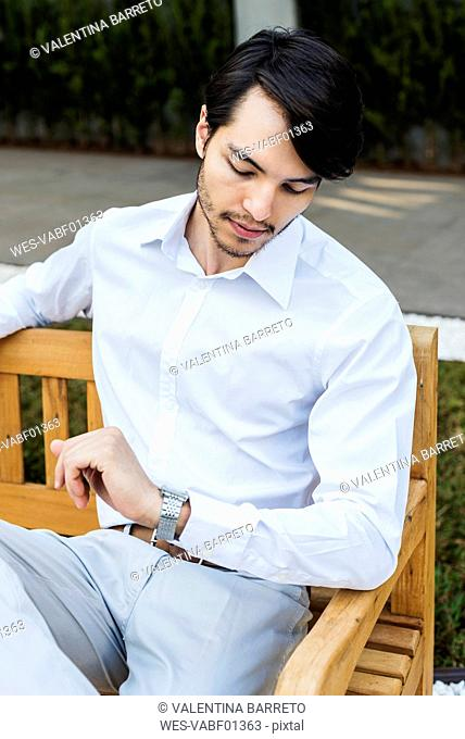 Businessman sitting on bench checking the time
