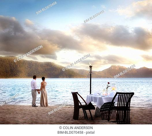 Couple next to table set for two at beach