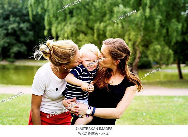 Young women kissing cute boy in park