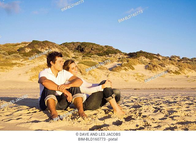 Caucasian couple relaxing on beach