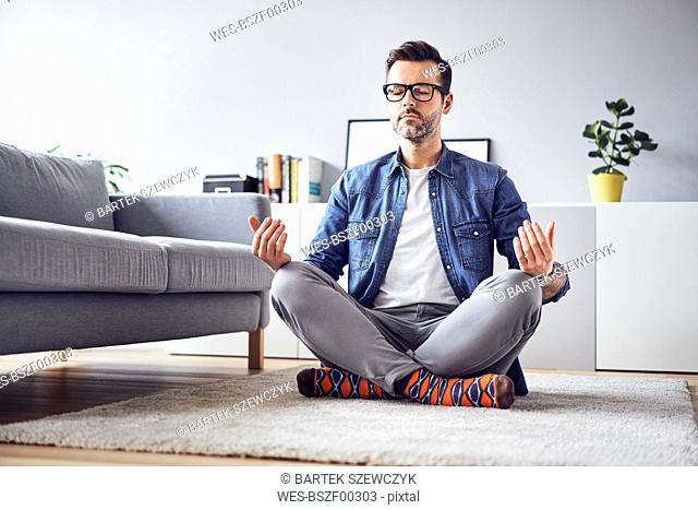 Relaxed man meditating at home