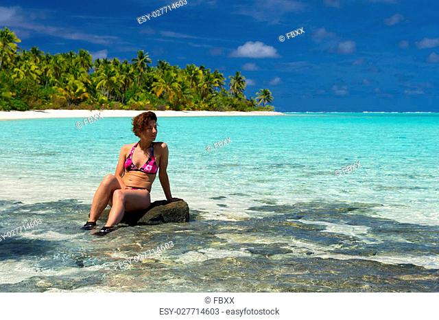 Woman sitting on dark rocks and watching the stunning colors of the sea surrounded by lush green palm groves on the remote One Foot Island, Aitutaki