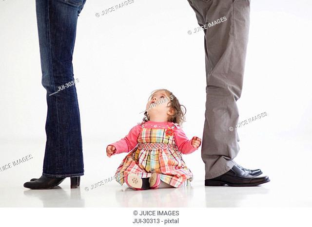 Baby girl sitting between parent's legs looking up