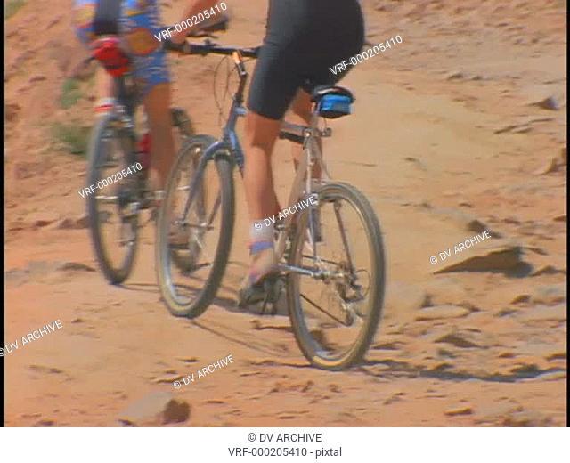 women ride mountain bikes along a desert trail