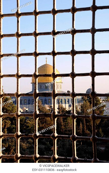 Dome of the Rock mosque view thru medrese window at sunset in Jerusalem, Israel