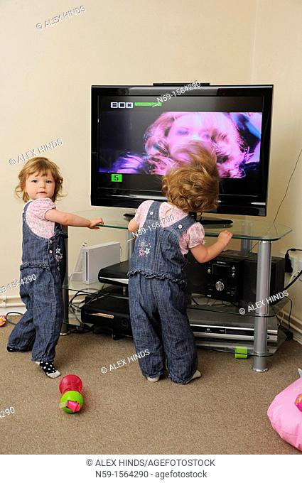 Twins watching TV at home