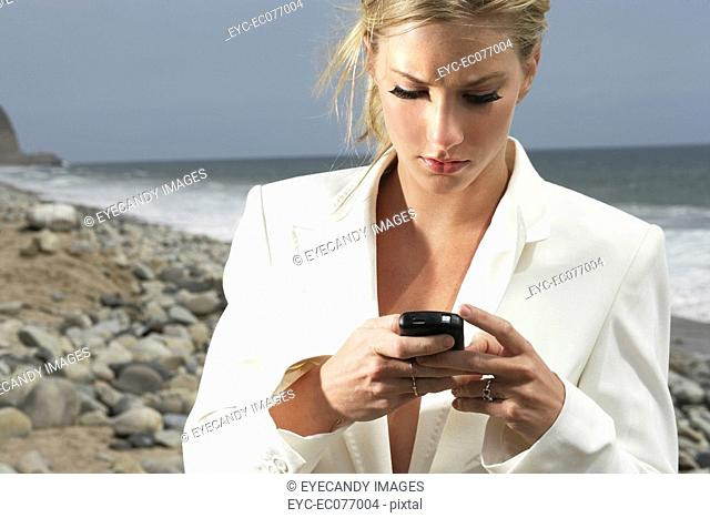 Young sexy businesswoman on the phone at the beach