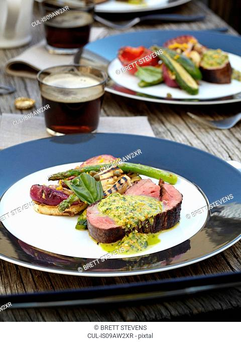 Close up of chimichurri Beef with barbecued salad outdoors on wooden garden table