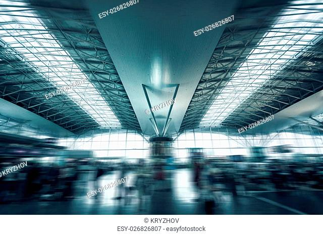 Photo of urban airport terminal with rushing passengers
