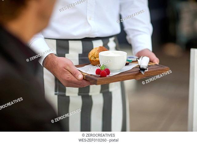 Waiter serving dessert at outdoor restaraunt