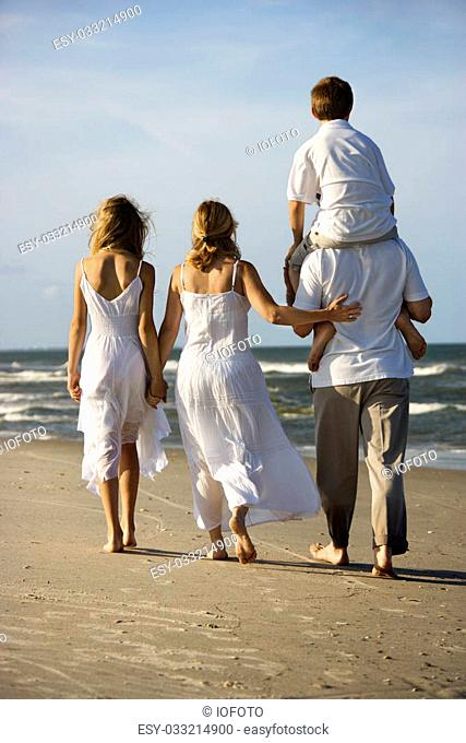 Caucasian family of four walking on beach with dad carrying son on shoulders