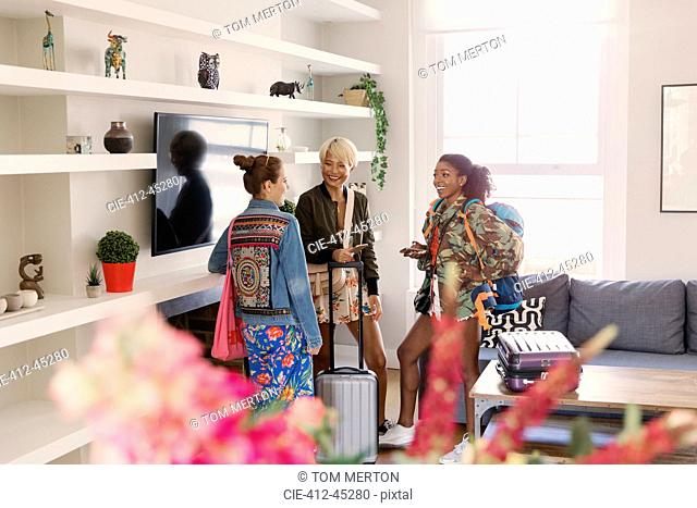 Young women friends with suitcases in house rental