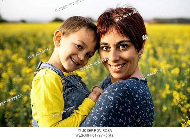 Portrait of mother and little son in a rape field