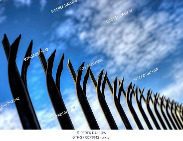 Spiked security fence against blue sky background