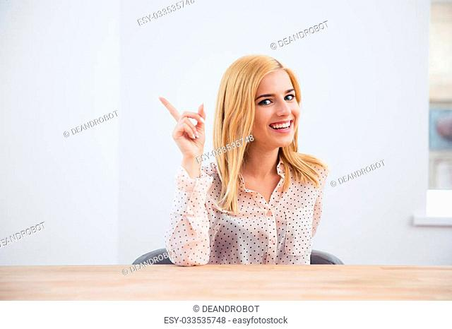 Happy young businesswoman sitting at the table and pointing finger up. Looking at camera
