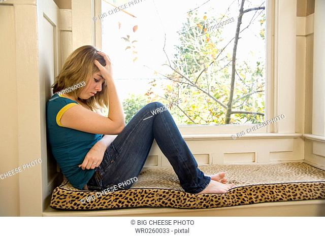 Teenaged girl sitting next to window