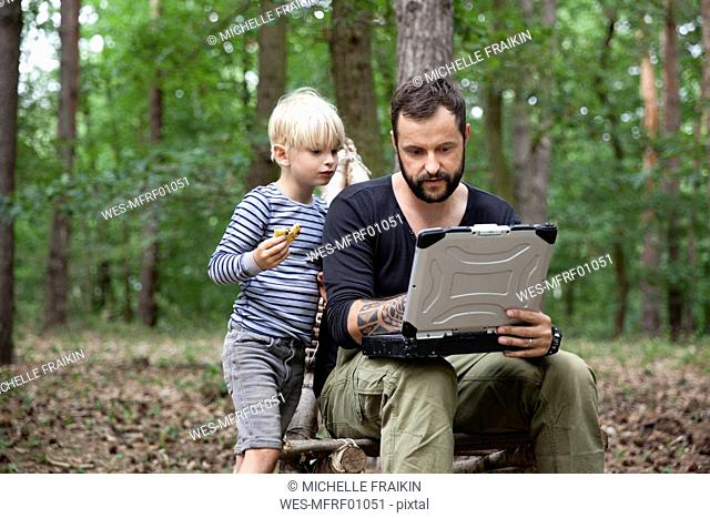 Father and son sitting on self-made wooden chair in forest using laptop