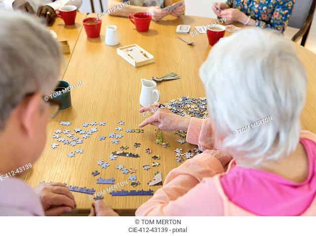 Senior friends assembling jigsaw puzzle at table in community center