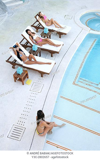 Four young women tanning and enjoying day at swimming pool