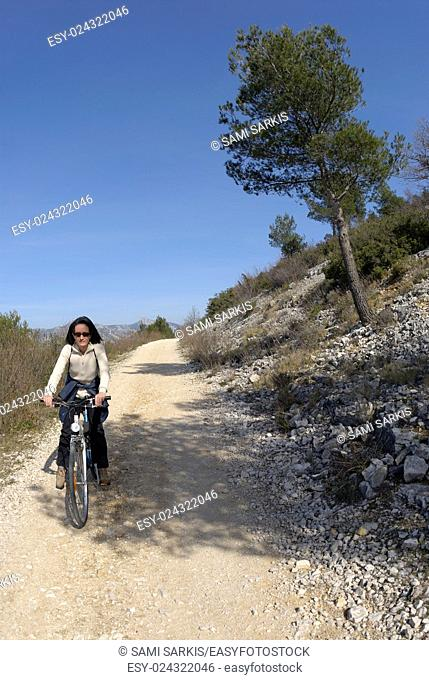 Woman riding a bike on a dirt, Provence, France, Europe