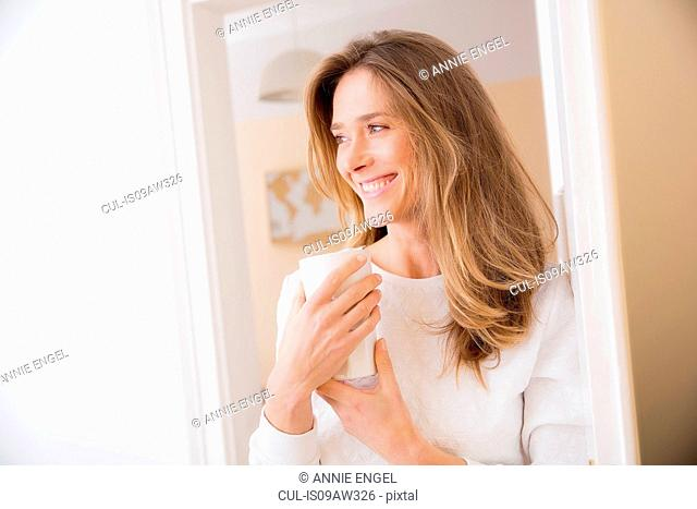 Mid adult woman leaning against doorway with mug