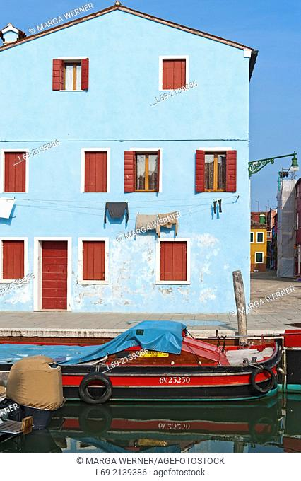 Canal with boat and blue house on island Burano, Venice, Italy,