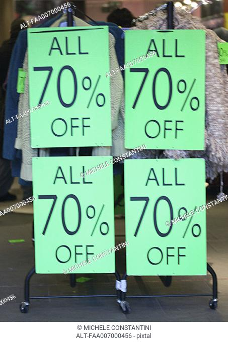 Signs on rack of clothing with text 'all 70 off'