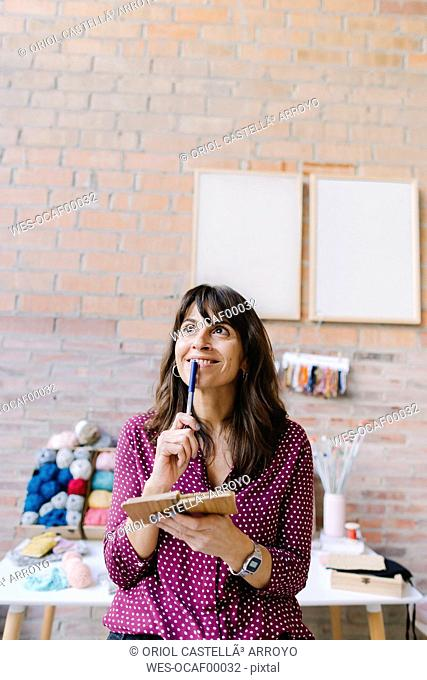 Smiling woman in knitting studio thinking and taking notes
