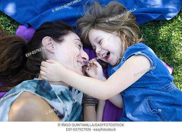 woman mother and four years old blonde child laughing together lying on towels in the green grass of park
